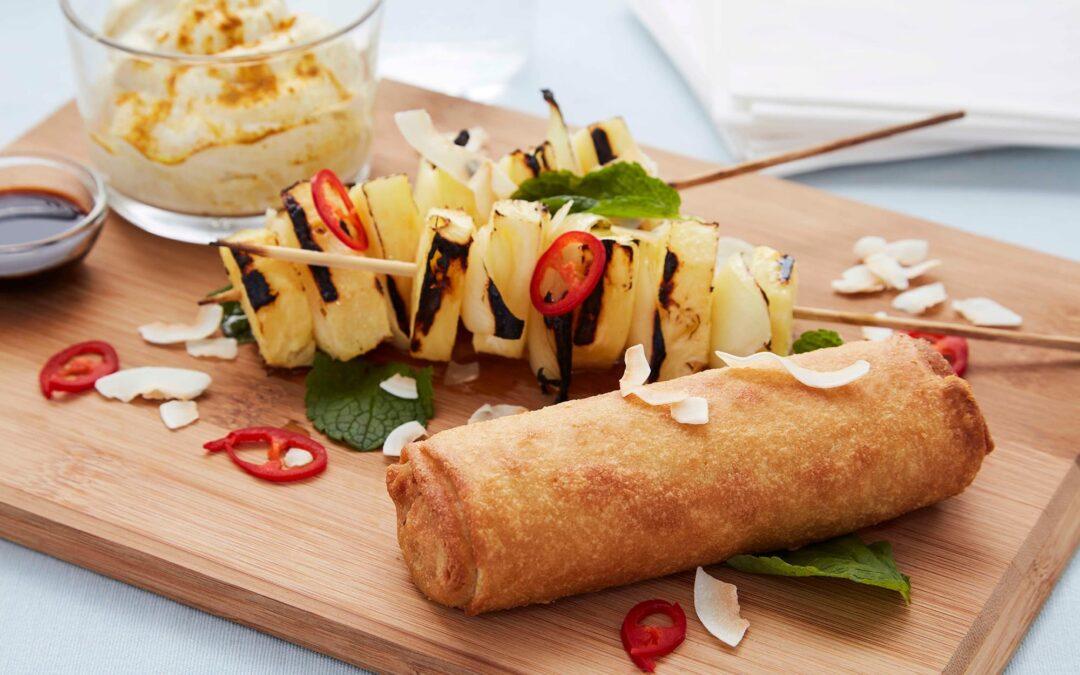 Frühlingsrollen mit Gemüse, serviert mit gegrillter Ananas
